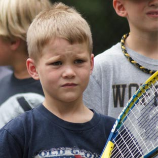 A camper prepares himself for an upcoming tennis match.