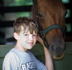 Hanging out with the horses is one of the highlights of this camper's summer.