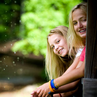 Two smiling girls at an overnight summer camp