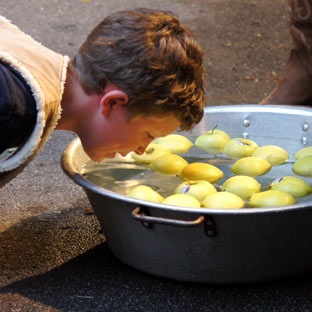 A boy at a summer camp bobs for apples