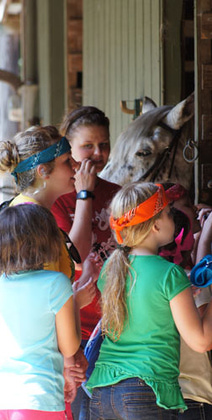 Counselors and campers visit one of Camp Highlander's horses