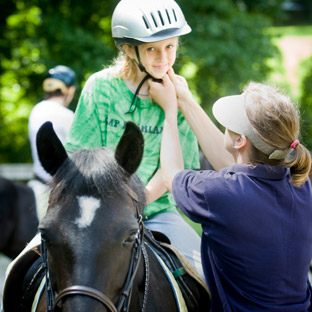 A counselor adjusts a young rider's helmet on horseback