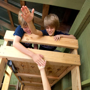 Boys give each other high fives in their summer camp cabin