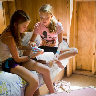 Two girls visit in their summer camp cabin at Highlander