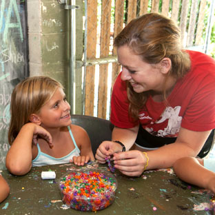 A camper and counselor laugh over crafts