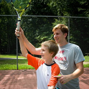 A college-age counselor shows a boy how to swing a tennis racket